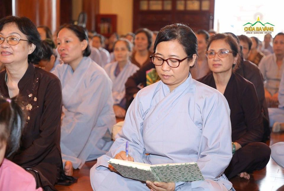 Các Phật tử chăm chú lắng nghe và ghi lại những lời giảng từ Sư Phụ