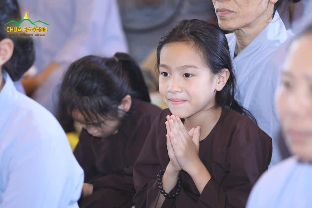 Em bé gái chắp tay thành kính trang nghiêm trong thời khóa truyền bát quan trai giới