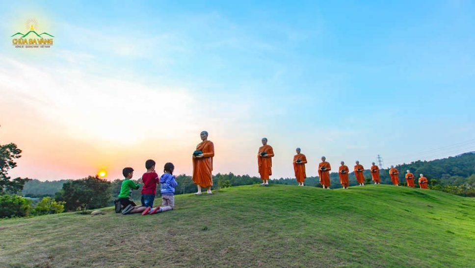 Các em nhỏ thành kính đảnh lễ 10 pho tượng các vị Sa môn tại lỗi rẽ vào cổng chùa