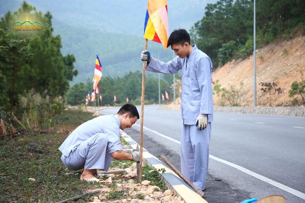 Hai bạn trẻ hoan hỷ khi được đi treo cờ hai bên con đường lên chùa
