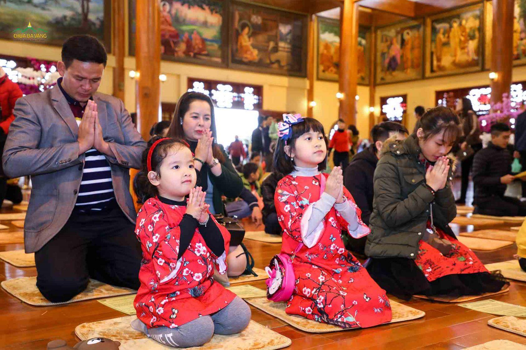 Những em bé theo bố mẹ đi chùa đang chắp tay trước ban Tam Bảo