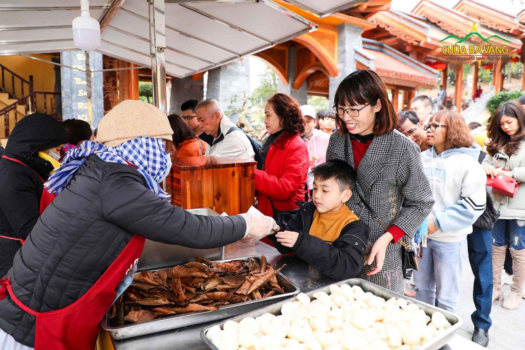 Du khách rất hào hứng với những đồ ăn được phát miễn phí tại điểm thỉnh lộc của chùa