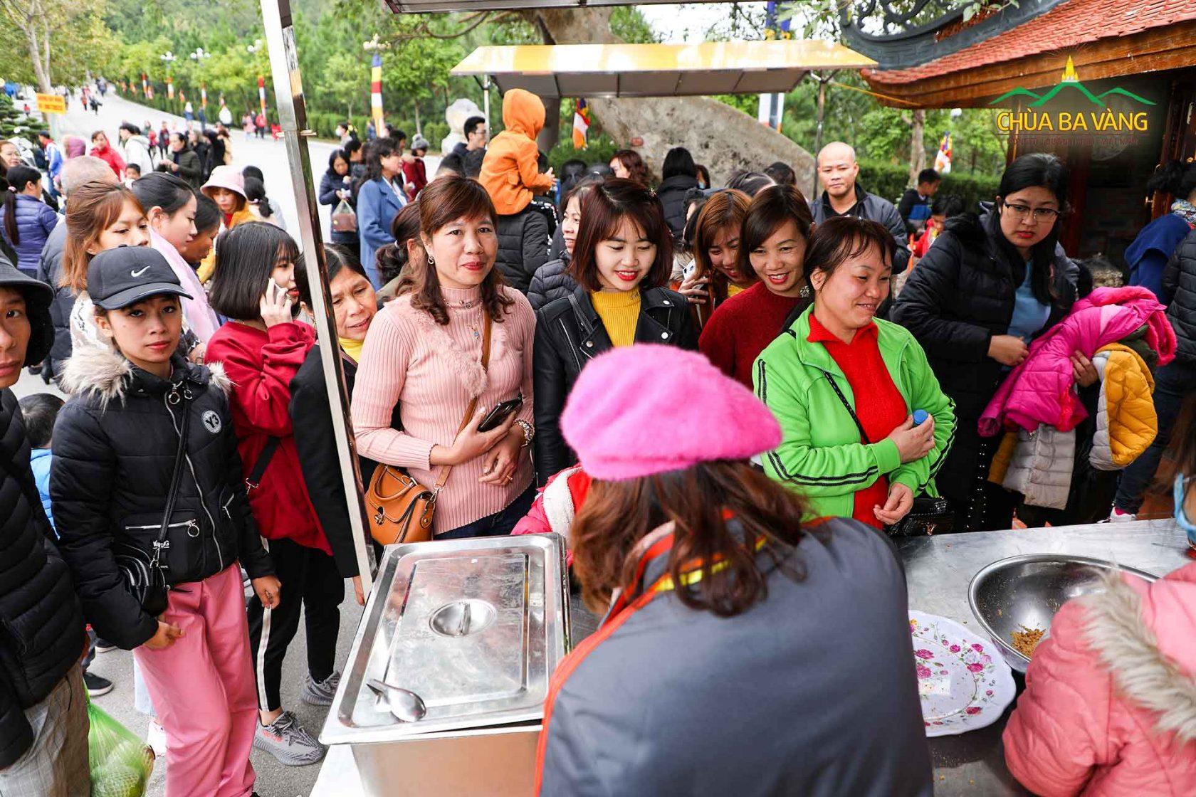 Du khách xếp hàng dài để xin bánh Samosa tại các điểm phát lộc của chùa