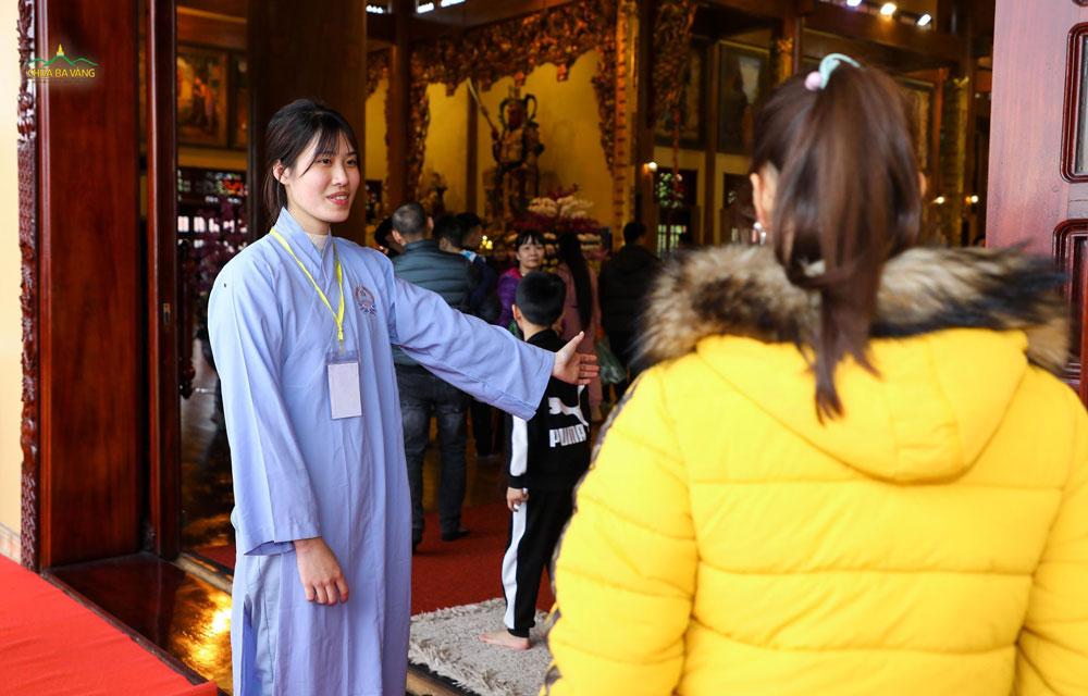 Phật tử trong ban Hương Đăng hướng dẫn khách khi vào trong Chính điện
