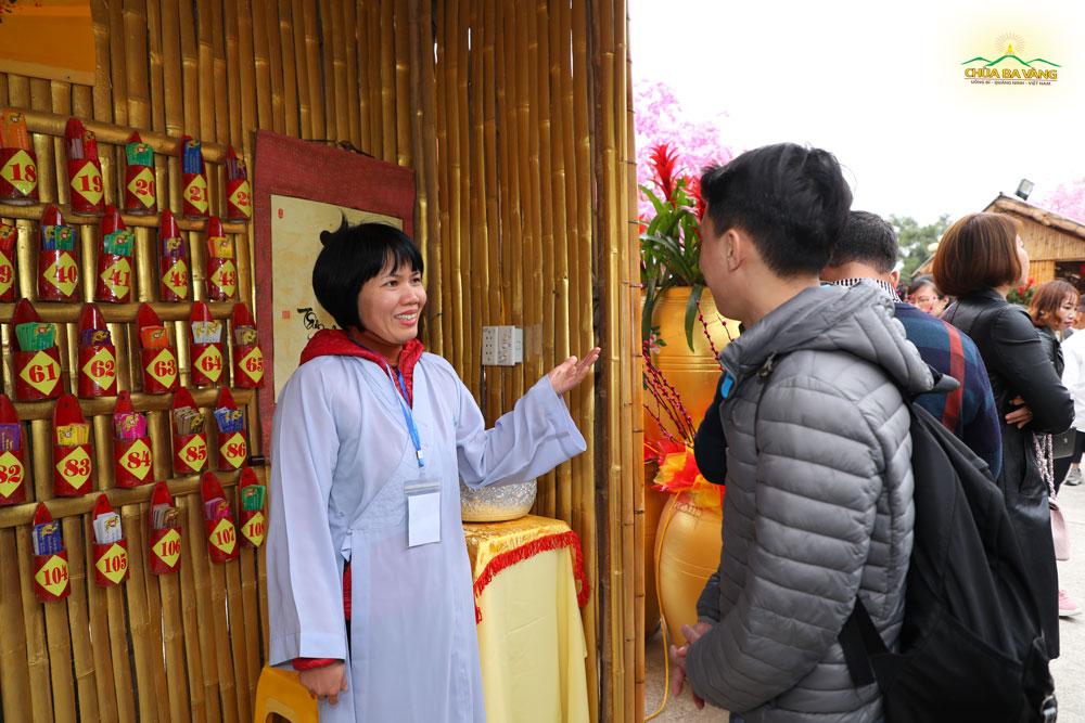 Cô Phật tử hoan hỷ hướng dẫn du khách xin lời Phật dạy