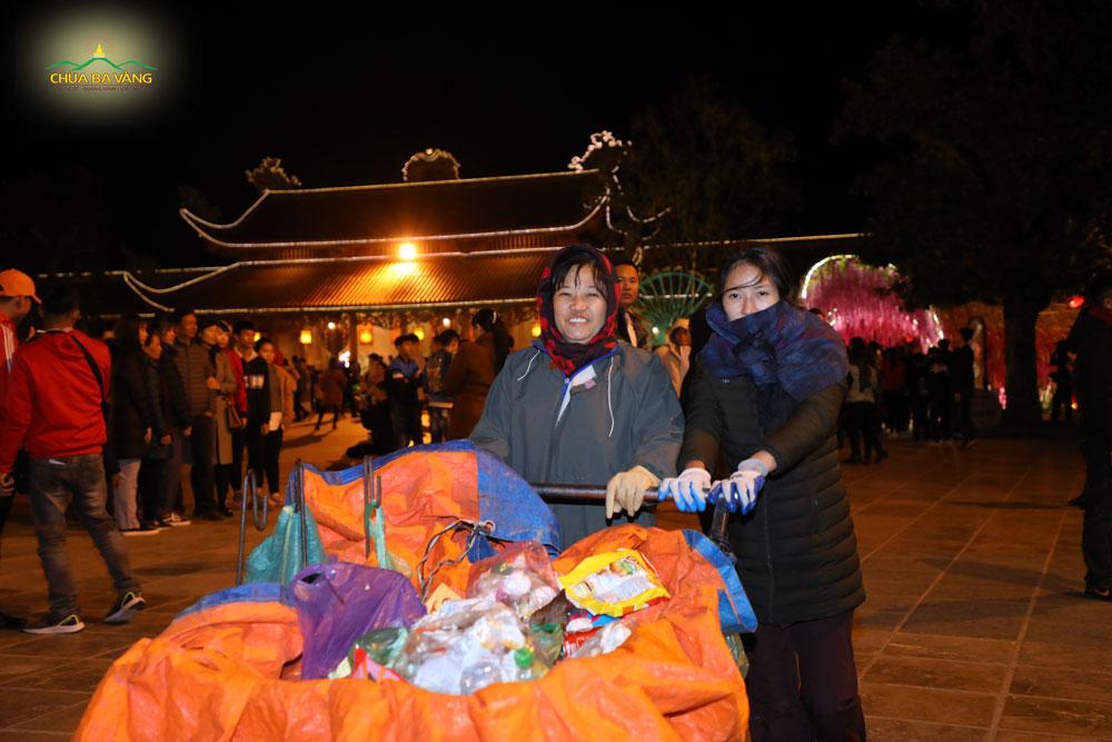 Chị Trần Ngọc Oanh (bên trái) đang đi thu gom rác trong khuôn viên chùa