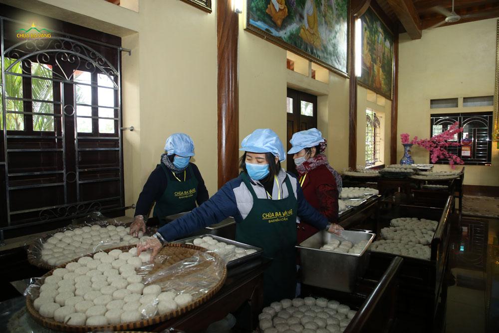 Các cô, bác Phật tử đang xếp cơm nắm vào khay để chuyển đến các điểm thỉnh lộc miễn phí của chùa