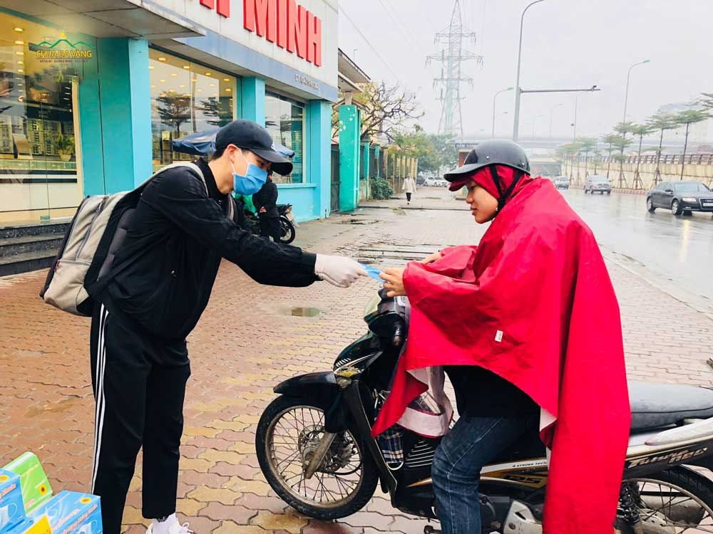 Mặc dù thời tiết mưa rét, bạn trẻ vẫn hăng hái phát khẩu trang cho người đi đường