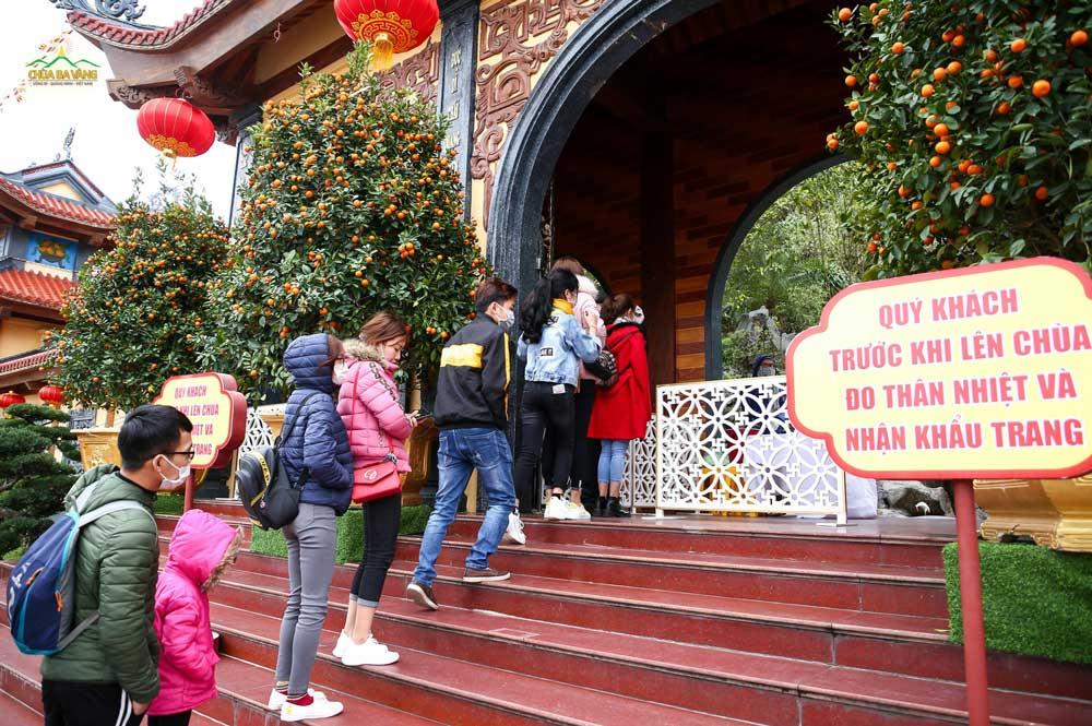 Ngay từ cổng Tam Quan nhà chùa đã bố trí sẵn các điểm đo thân nhiệt và phát khẩu trang miễn phí dành cho du khách