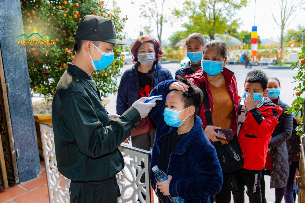 Du khách lần lượt xếp hàng để kiểm tra thân nhiệt trước khi vào chùa tham quan, lễ Phật