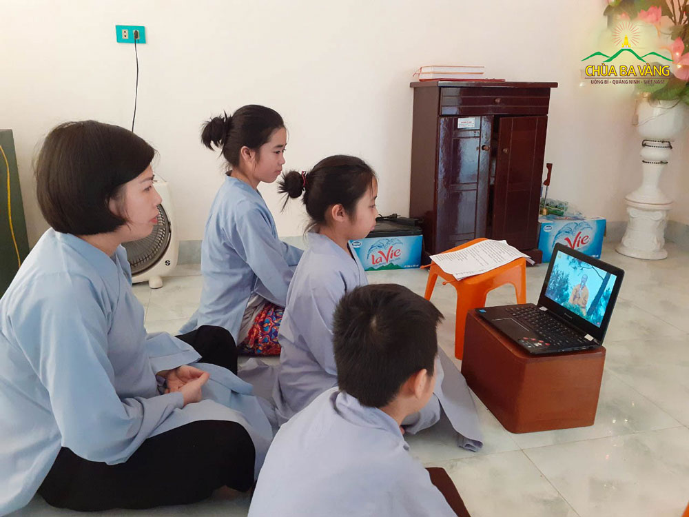 Phật rử nhí Khánh Vi cùng mẹ và các em chăm chú lắng nghe Sư Phụ giảng Pháp qua mạng