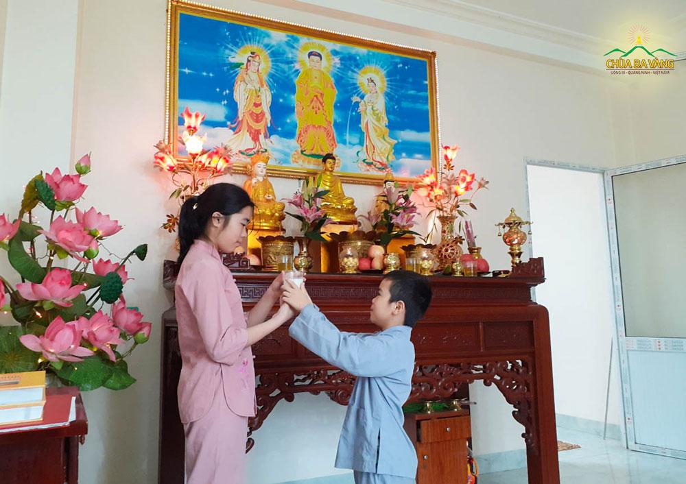 Khánh Vi cùng em trai dâng phẩm vật thanh tịnh dâng lên cúng dường Tam Bảo
