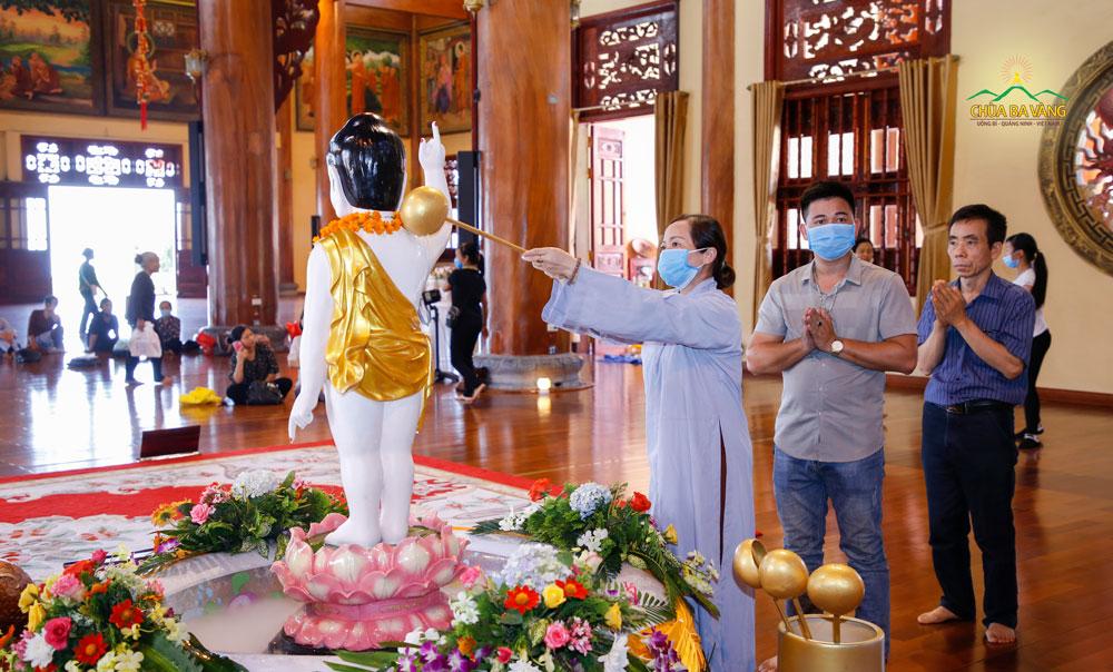 Phật tử và du khách thực hiện nghi lễ tắm Phật tại tầng 2 Chính điện chùa Ba Vàng