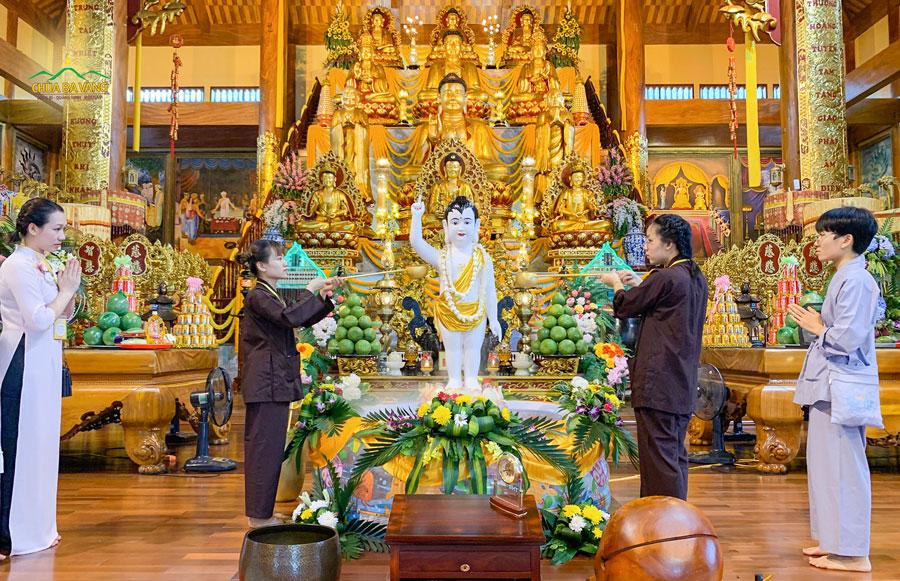 Các thành viên trong CLB Tuệ Tâm thực hiện nghi lễ tắm Phật tại tầng 2 Chính điện chùa Ba Vàng