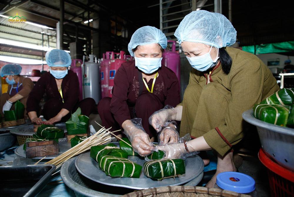 Các Phật tử cùng nhau gói những chiếc bánh chưng chay thật đẹp để dâng cúng dường Tam Bảo, cúng dường chư Tăng
