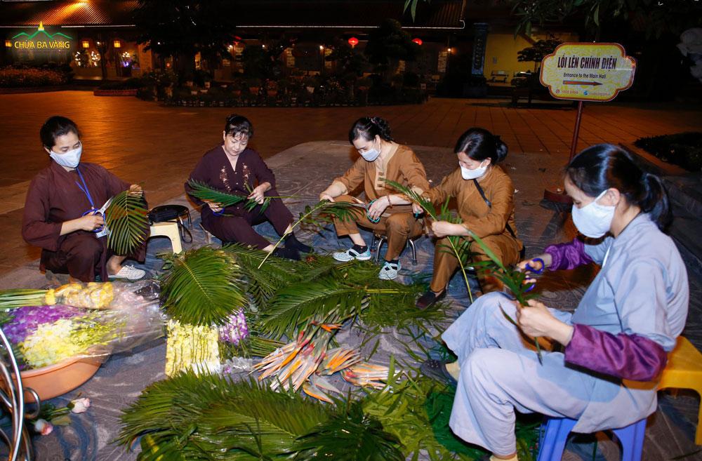 Các Phật tử cùng nhau cắm những lẵng hoa tươi thắm trăng bày trong ngày tu học