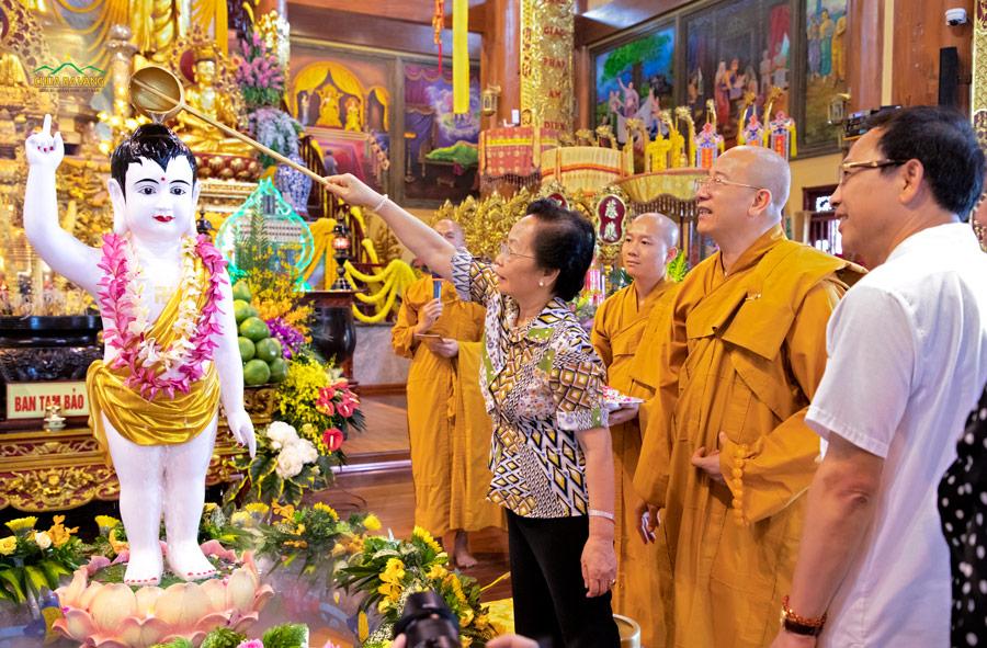 Bà Nguyễn Thị Doan thực hiện nghi lễ tắm Phật tại Chính điện tầng 2 chùa Ba Vàng