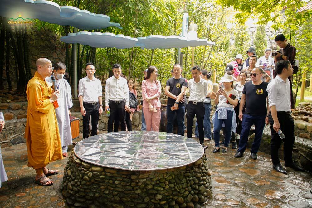 Đại Đức Thích Trúc Bảo Thành giới thiệu cho phái đoàn về giếng Thần linh thiêng của chùa Ba Vàng