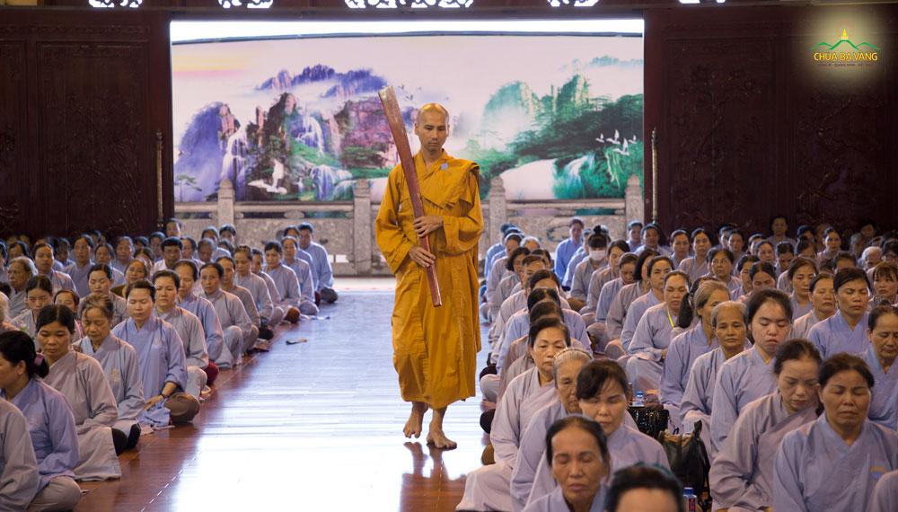 Đại đức Thích Trúc Bảo Tín đi giám thiền, chỉnh lại tư thế ngồi thiền cho Phật tử