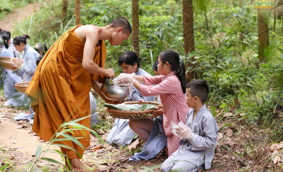 Phật tử nhí kính cẩn dâng vật phẩm cúng dường chư Tăng trong niềm hoan hỷ