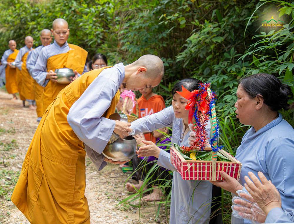 Phật tử cung kính dâng vật phẩm cúng dường vào bình bát của chư Ni