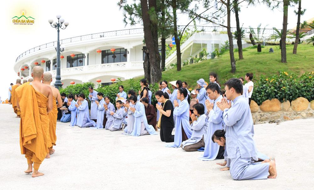 Phật tử Nguyễn Ngọc Công quỳ khối chắp tay trang nghiêm khi tham dự chương trình sớt bát cúng dường chư tăng tại chùa Ba Vàng