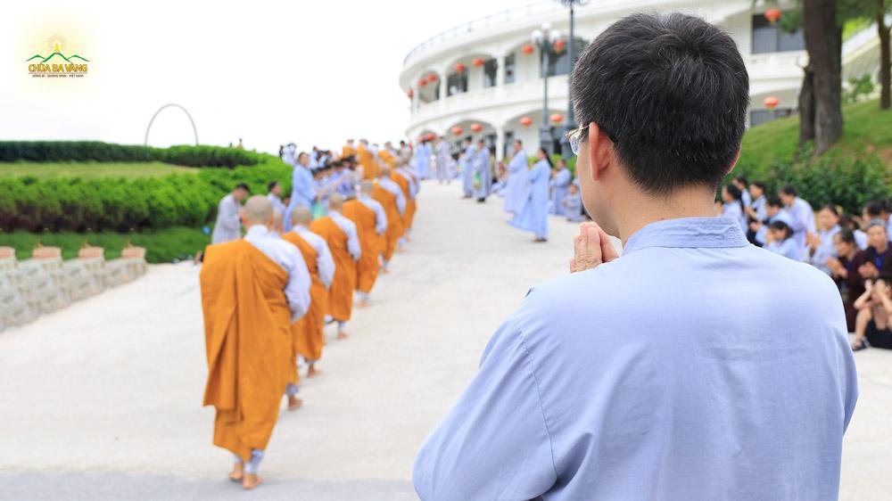 Phật tử Nguyễn Công Hoan chắp tay thành kính khi chứng kiến Tăng đoàn ôm bình bát trì bình khất thực tại khuôn viên chùa Ba Vàng