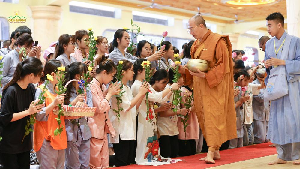 Các bạn trẻ thành kính dâng hoa và vật thực cúng dường lên Sư Phụ cùng chư Tăng