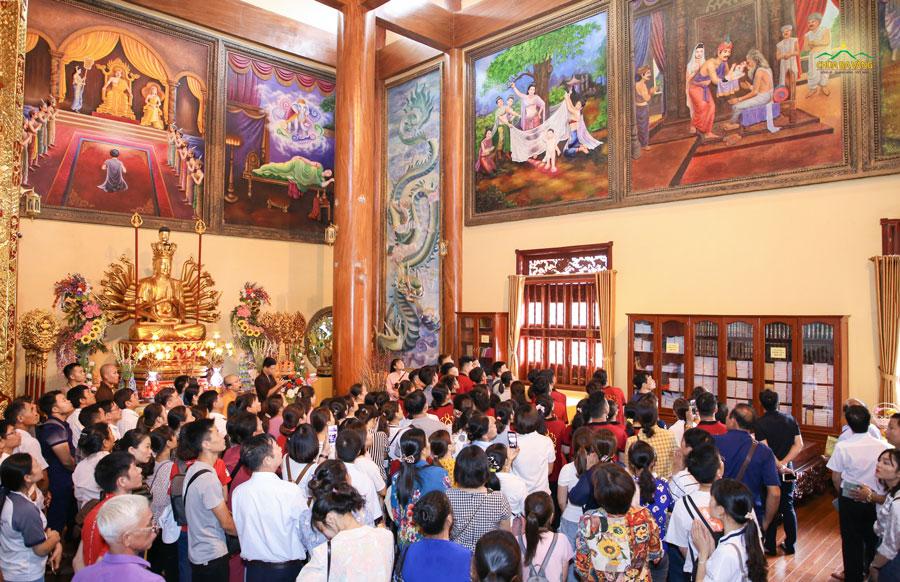 Các thành viên trong Công ty bảo hiểm AIA chi nhánh miền Bắc lắng nghe quý Thầy giới thiệu về cuộc đời Đức Phật qua 37 bức tranh tại chính điện chùa Ba Vàng