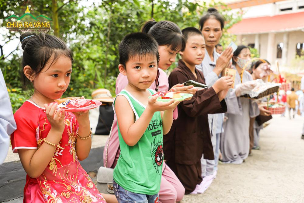 Các em nhỏ hai tay thành kính dâng phẩm vật đón đợi Tăng đoàn khất thực