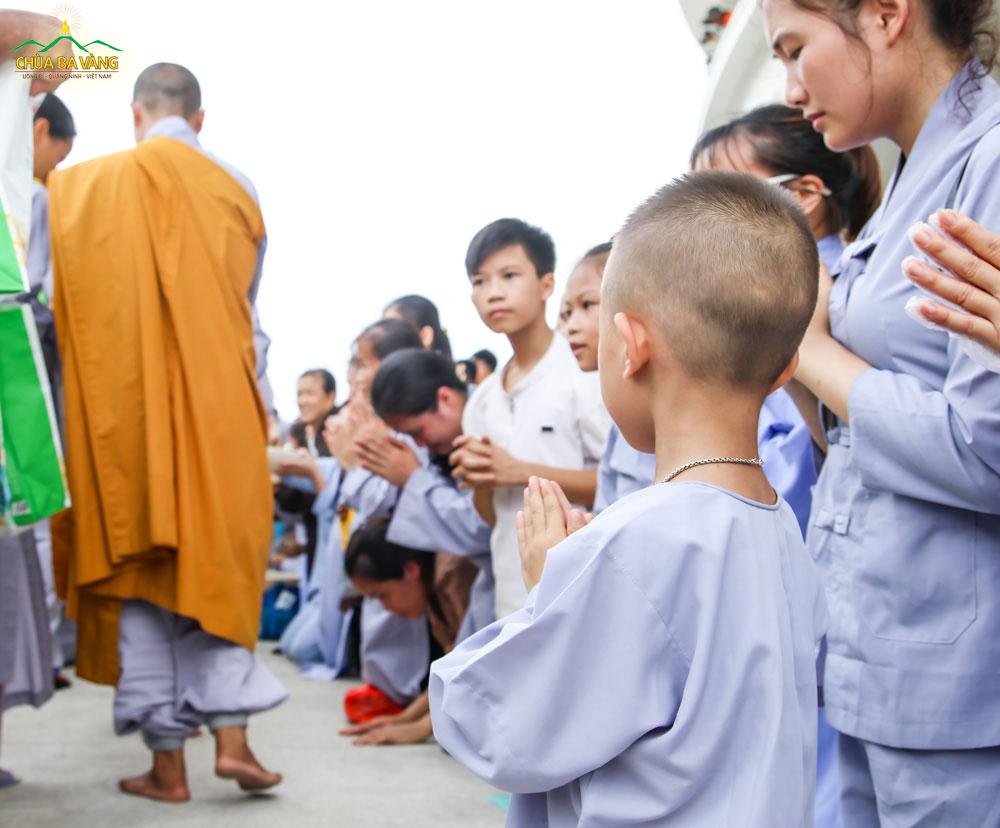 Phật tử nhí cung kính chắp tay khi chứng kiến hình ảnh Tăng đoàn trì bình khất thực