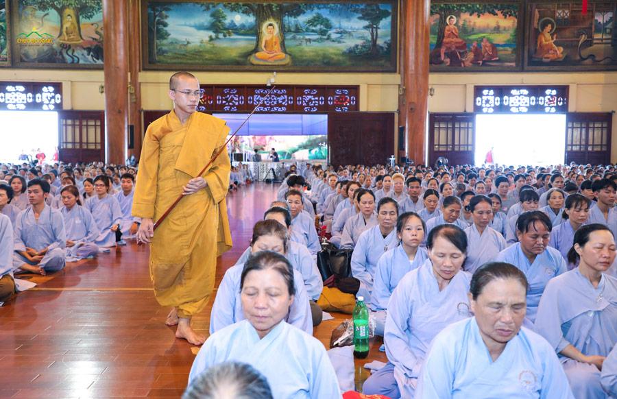 Đại đức Thích Trúc Bảo Kiên đi giám thiền, chỉnh lại tư thế ngồi thiền cho Phật tử