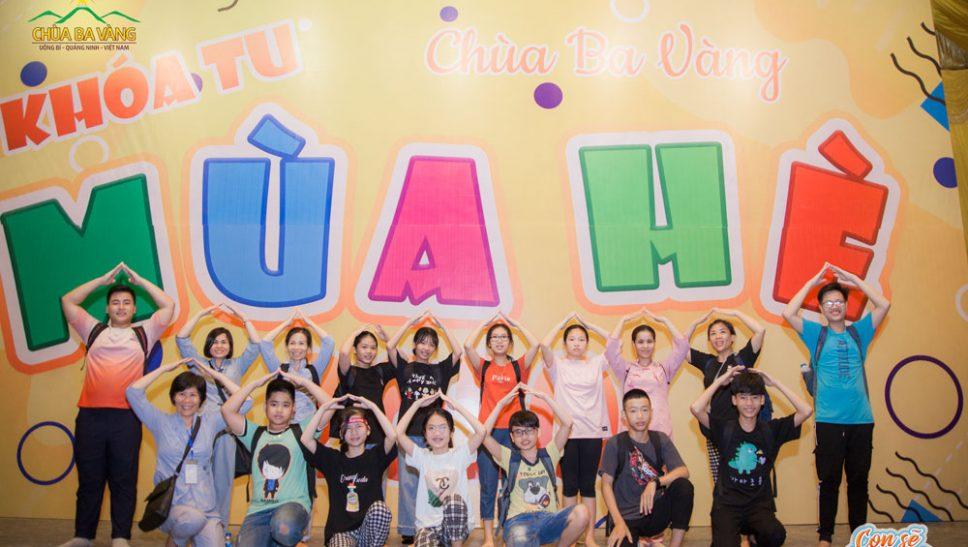 """Các bạn nhỏ vui vẻ chụp ảnh trước banner """"Khóa tu mùa hè 2020"""" tại sân Chính điện chùa Ba Vàng"""