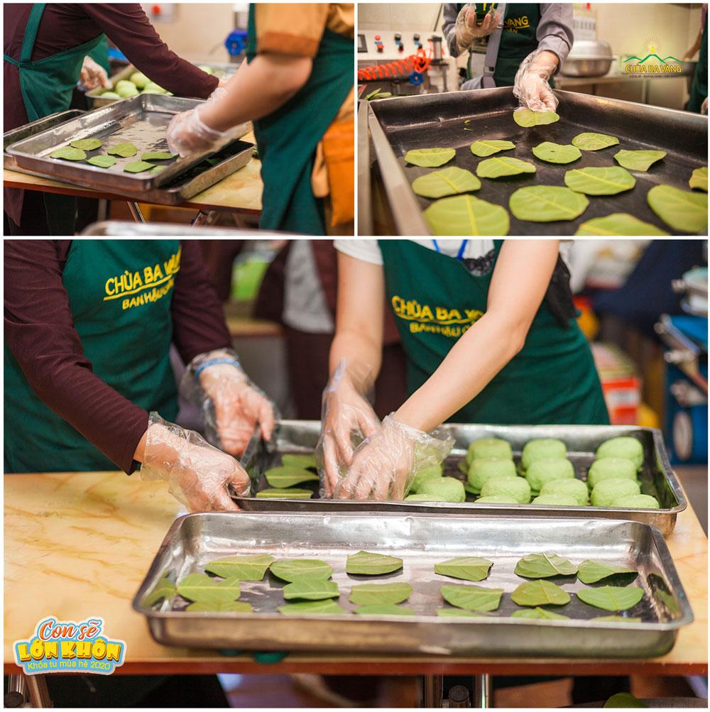 Các Phật tử đặt những chiếc bánh bao lên lá trước khi đưa vào lò hấp