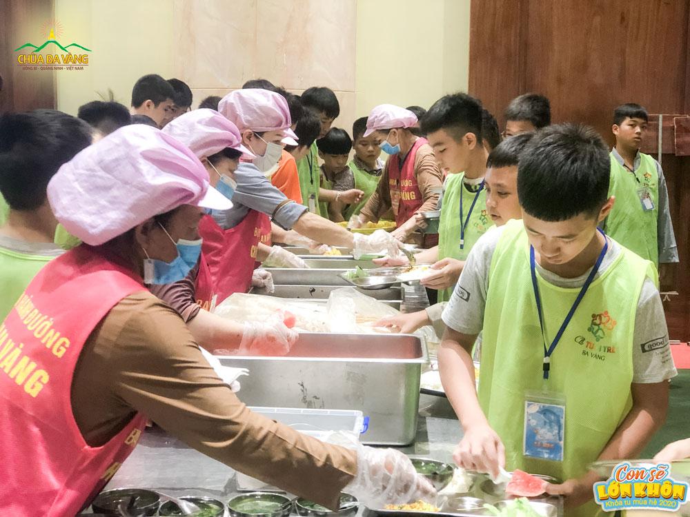 Các cô bác Phật tử Ban hành đường chia phần ăn cho các bạn khóa sinh