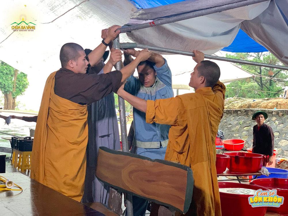Quý Thầy hỗ trợ Phật tử cột lại bạt che mưa nơi rửa bát của các bạn khóa sinh