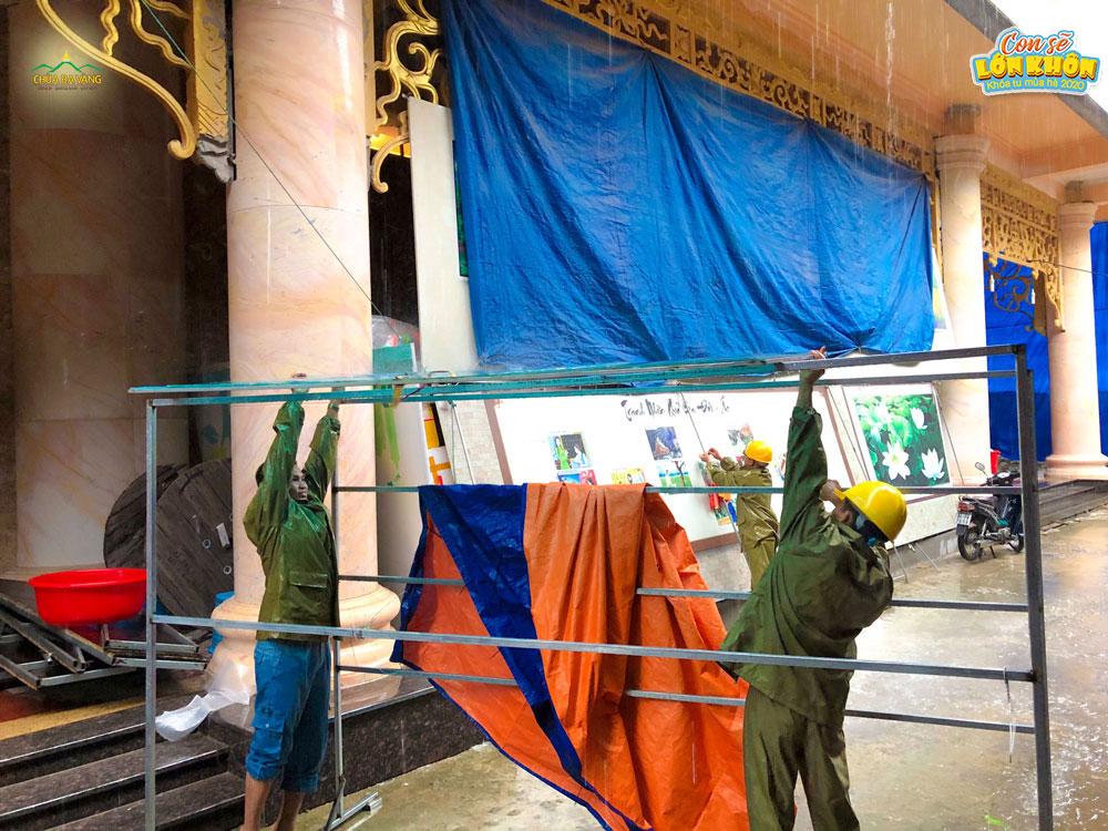 Các Phật tử dựng bạt tạo cung đường tránh mưa cho các khóa sinh