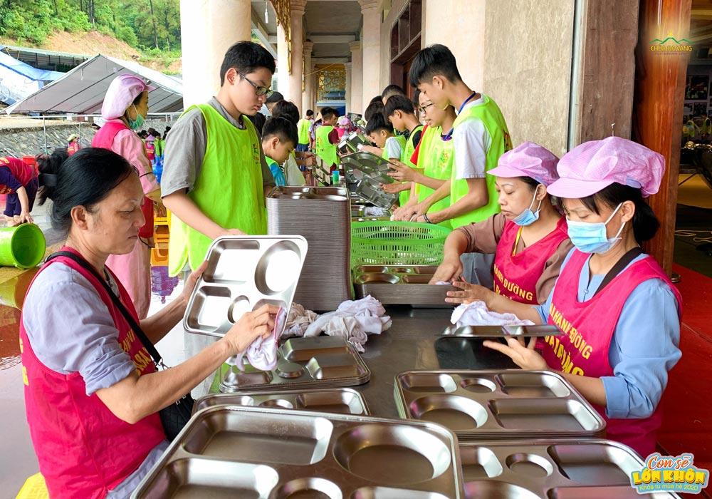 Các cô bác trong Ban Hành đường lau những chiếc khay ăn thật sạch sẽ để đảm bảo cho khóa sinh có bữa cơm ngon miệng