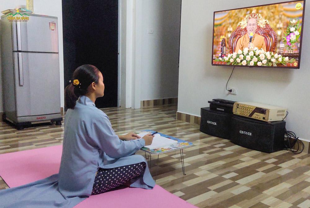 Cô Phật tử chăm chú lắng nghe và ghi lại ý nghĩa của bài kinh Tam Bảo