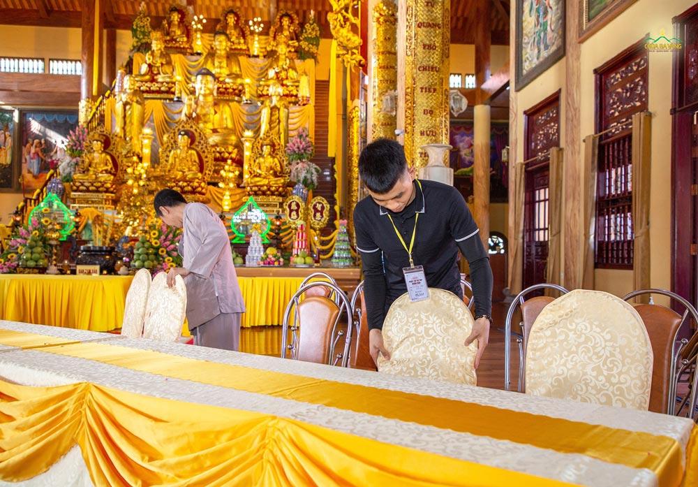 Phật tử sắp xếp bàn ghế tại Chính điện để chuẩn bị cho lễ giỗ Tổ